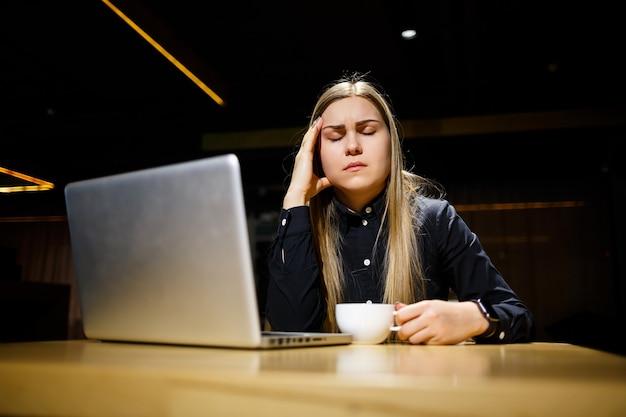 Un jeune homme d'affaires est assis devant l'ordinateur et a mal à la tête après une longue journée de travail