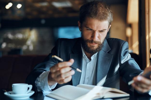 Jeune homme d'affaires est assis à une table avec des papiers et boit du café, regarde par la fenêtre