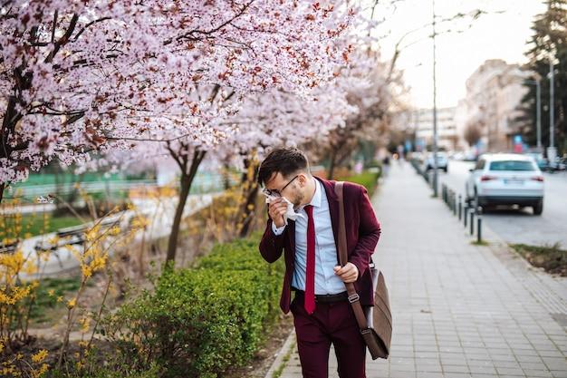 Jeune homme d'affaires éternuant dans le parc. allergie, grippe, concept de virus.