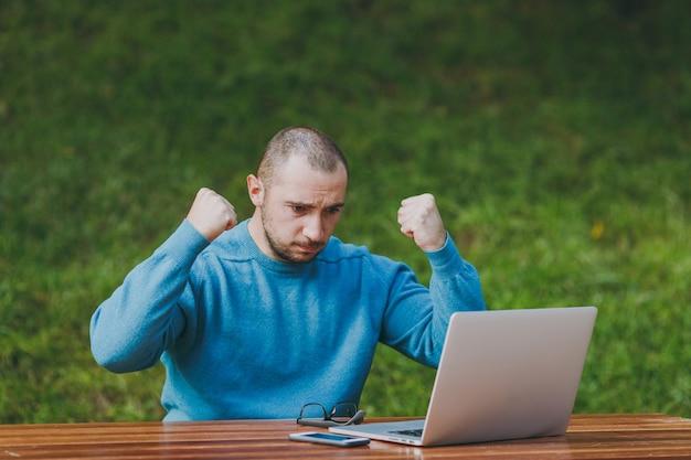 Un jeune homme d'affaires ou un étudiant choqué en colère en colère dans des lunettes de chemise bleue décontractée assis à table dans un parc de la ville utilise un ordinateur portable à l'extérieur levant les mains préoccupées par les problèmes. concept de bureau mobile.