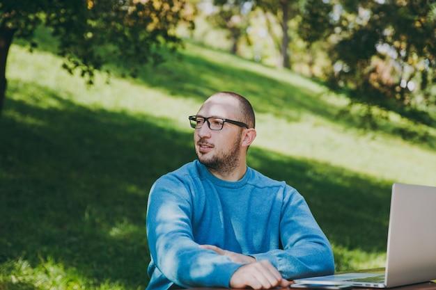 Jeune homme d'affaires ou étudiant intelligent réussi en chemise bleue décontractée, lunettes assis à table avec téléphone portable dans le parc de la ville à l'aide d'un ordinateur portable, travaillant à l'extérieur, regardant de côté. concept de bureau mobile.