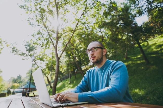 Jeune homme d'affaires ou étudiant intelligent réussi dans des lunettes de chemise bleue décontractée assis à table avec un téléphone portable dans le parc de la ville à l'aide d'un ordinateur portable travaillant à l'extérieur sur la nature verdoyante. concept de bureau mobile.