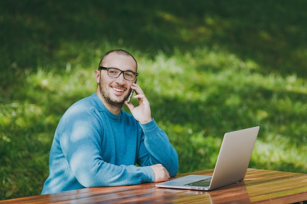 Jeune homme d'affaires ou étudiant souriant réussi en chemise bleue décontractée, lunettes assis à table, parlant au téléphone portable dans le parc de la ville à l'aide d'un ordinateur portable, travaillant à l'extérieur. concept de bureau mobile.