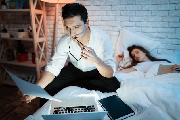 Jeune homme d'affaires étudie les graphiques sur ordinateur portable