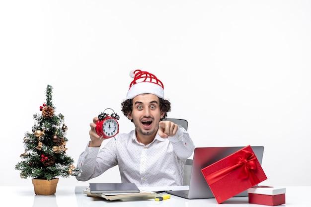 Jeune homme d'affaires excité avec chapeau de père noël et montrant l'horloge travaillant seul assis au bureau sur fond blanc
