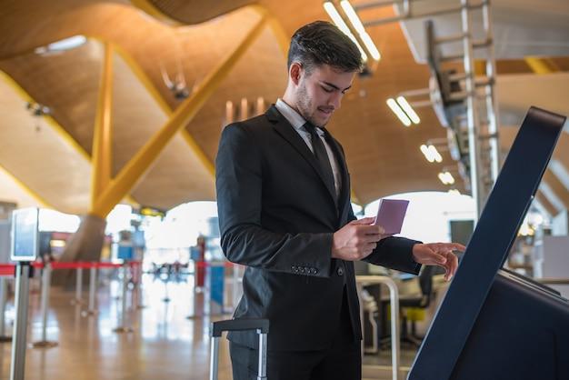 Jeune homme d'affaires faisant l'auto-vérification dans une machine à l'aéroport