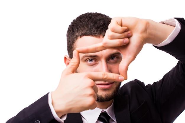 Jeune homme d'affaires faisant le cadre de la main, isolé sur un mur blanc