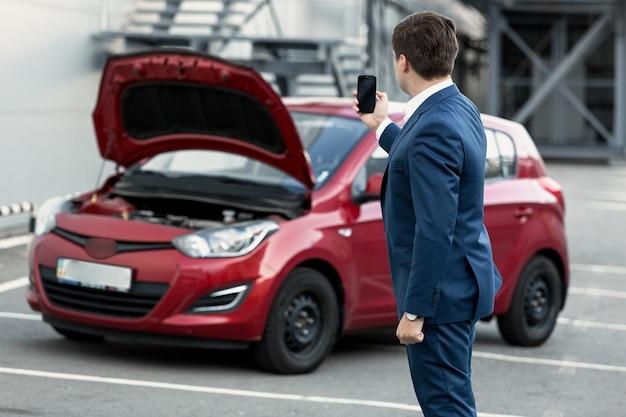 Jeune homme d'affaires faisant la photo sur le téléphone de la voiture de panne pour la compagnie d'assurance