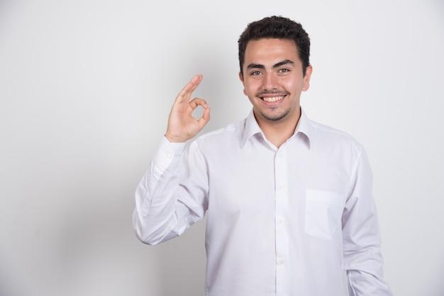 Jeune homme d'affaires faisant signe ok d'une main sur fond blanc.