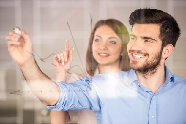 Jeune homme d'affaires et femme d'affaires dessiner un graphique.