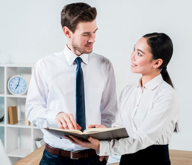 Jeune homme d'affaires et femme d'affaires discutant du projet dans l'agenda en se regardant