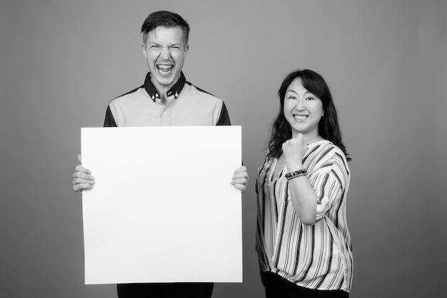 Jeune homme d'affaires et femme d'affaires japonaise mature ensemble contre le gris en noir et blanc