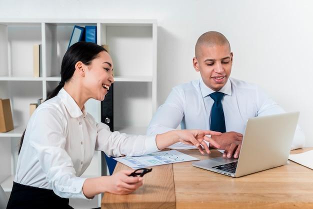 Jeune homme d'affaires et femme d'affaires à la recherche sur un ordinateur portable discutant du projet