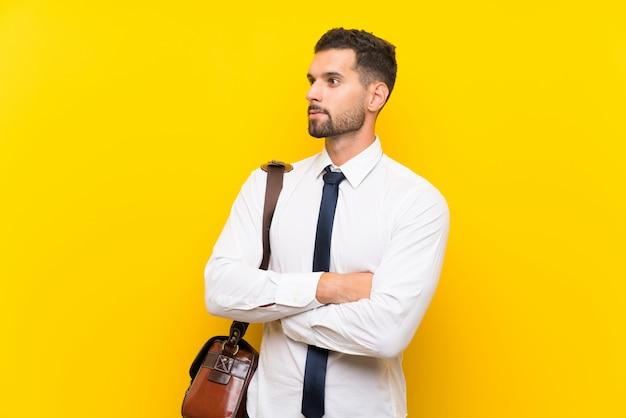 Jeune homme d'affaires sur fond jaune isolé