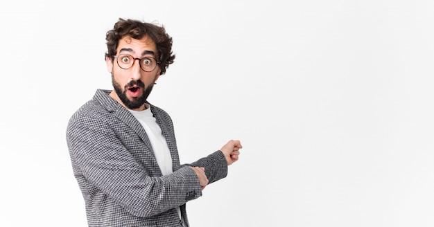 Jeune homme d'affaires fou se sentant choqué et surpris, pointant pour copier l'espace sur le côté avec un regard étonné et bouche ouverte contre le mur plat