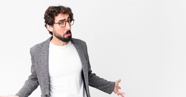 Jeune homme d'affaires fou se sentant désemparé et confus, n'ayant aucune idée, absolument perplexe avec un regard stupide ou stupide