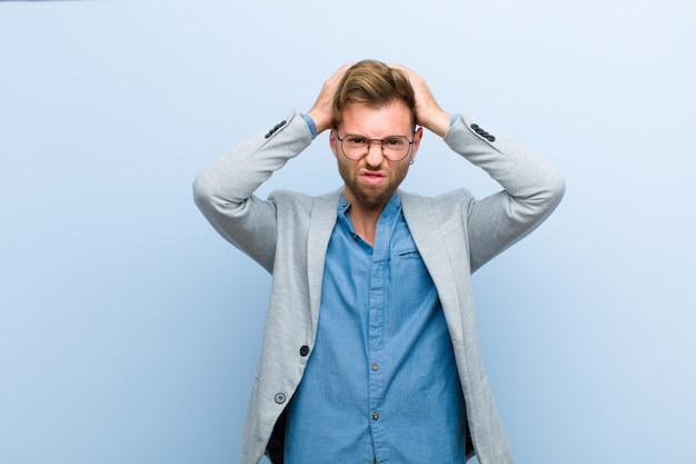 Jeune homme d'affaires frustré et agacé, malade et fatigué de l'échec, marre des tâches ennuyeuses et ennuyeuses sur fond bleu