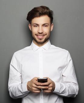 Jeune homme d'affaires gai tapant sms sur son téléphone portable