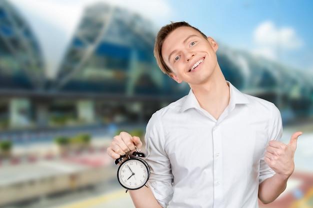 Jeune homme d'affaires garde l'horloge