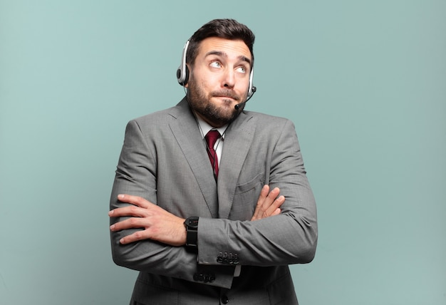 Jeune homme d'affaires haussant les épaules, se sentant confus et incertain, doutant avec les bras croisés et le concept de télémarketing regard perplexe