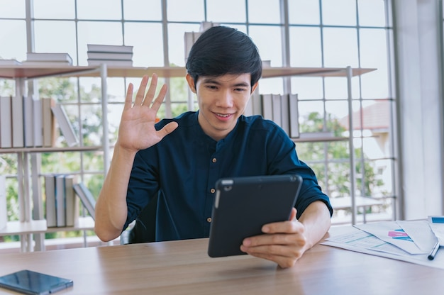 Jeune homme d'affaires heureux appel vidéo souriant avec un ami à la maison. concept travail rester à la maison