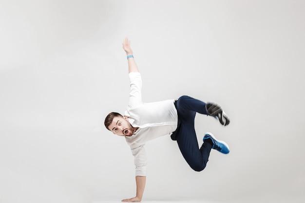 Jeune homme d'affaires heureux avec barbe en chemise break dance