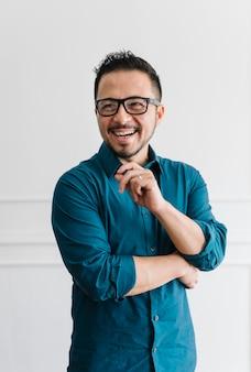 Jeune homme d'affaires heureux debout près d'un mur blanc