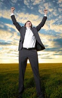 Jeune homme d'affaires heureux les mains dans le champ