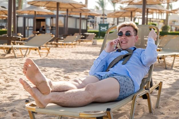 Un jeune homme d'affaires heureux parle au téléphone allongé sur une chaise longue au milieu de la b...