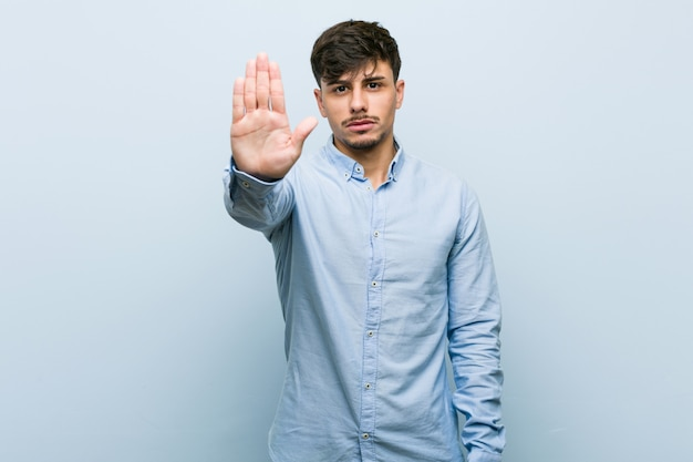 Jeune homme d'affaires hispanique debout avec la main tendue montrant le panneau d'arrêt, vous empêchant.