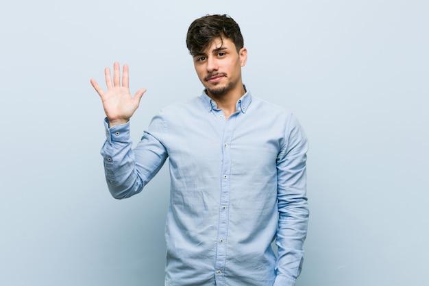 Jeune homme d'affaires hispanique souriant gai montrant le numéro cinq avec les doigts.