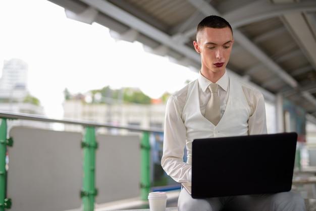 Jeune homme d'affaires homosexuel androgyne lgtb à l'aide d'un ordinateur portable