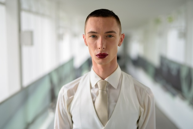 Jeune homme d'affaires homosexuel androgyne lgtb portant du rouge à lèvres
