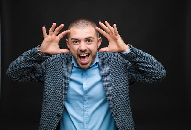 Jeune homme d'affaires hurlant de panique ou de colère, choqué, terrifié ou furieux, avec les mains à côté de la tête sur le mur