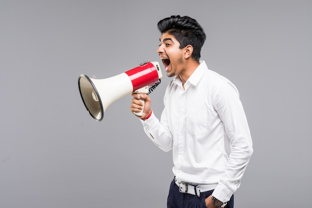 Jeune homme d'affaires indien annonçant dans un mégaphone sur mur gris