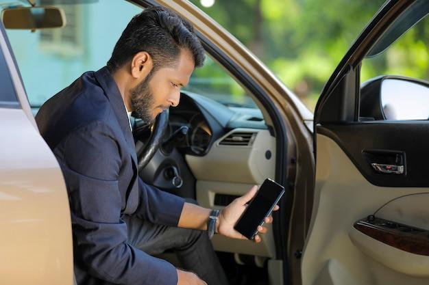 Jeune homme d'affaires indien assis à côté de la voiture et montrant l'écran du téléphone intelligent