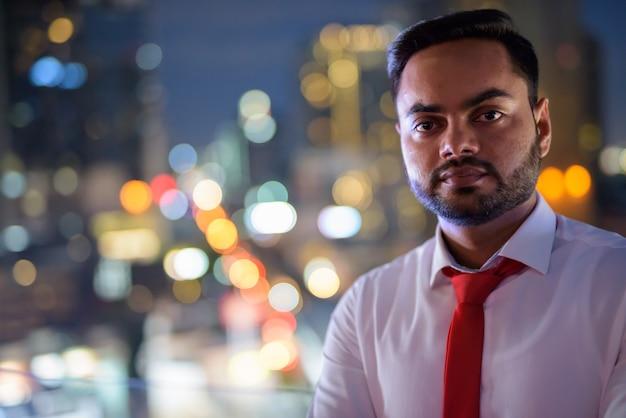 Jeune homme d'affaires indien barbu contre vue sur la ville pendant la nuit