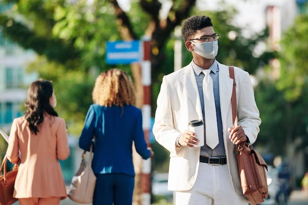Jeune homme d'affaires indien dans des verres et un masque médical à pied pour travailler avec une tasse de café du matin dans les mains