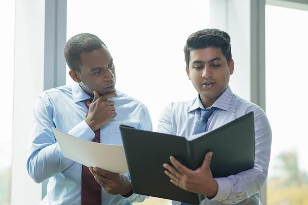 Jeune homme d'affaires indien lisant un document à voix haute pour collègue