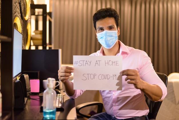 Jeune homme d'affaires indien avec masque montrant rester à la maison signer tout en travaillant des heures supplémentaires à la maison pendant la quarantaine