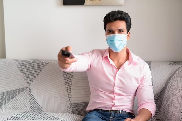 Jeune homme d'affaires indien avec masque à regarder la télévision et rester à la maison en quarantaine