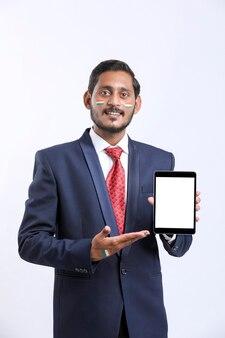 Jeune homme d'affaires indien montrant la tablette sur fond blanc.