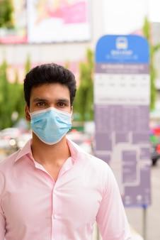 Jeune homme d'affaires indien portant un masque à l'arrêt de bus