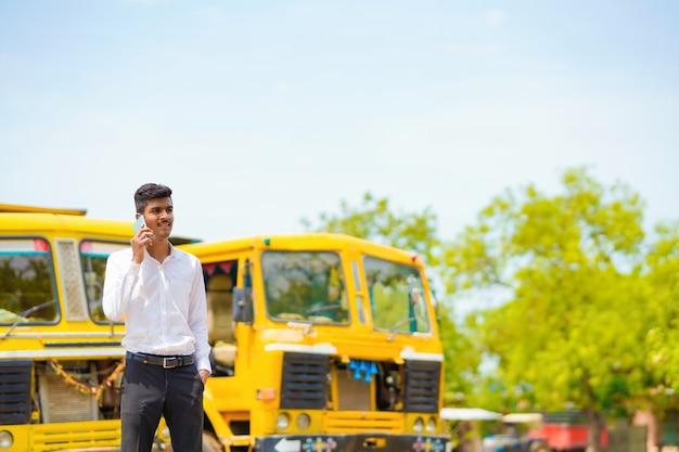 Jeune homme d'affaires indien avec son camion ou camion de fret et parlant sur smartphone.
