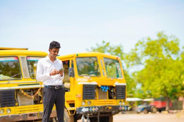 Jeune homme d'affaires indien avec son camion ou son camion de fret.