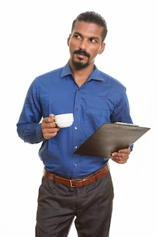 Jeune homme d'affaires indien tenant une tasse de café et un presse-papiers en pensant