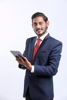 Jeune homme d'affaires indien utilisant une tablette sur fond blanc.