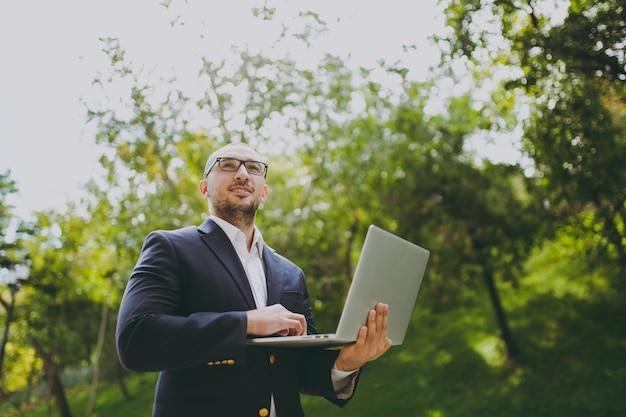 Jeune homme d'affaires intelligent réussi en chemise blanche, costume classique, lunettes. homme debout et travaillant sur un ordinateur portable dans un parc de la ville à l'extérieur sur fond de nature. bureau mobile, concept d'entreprise.