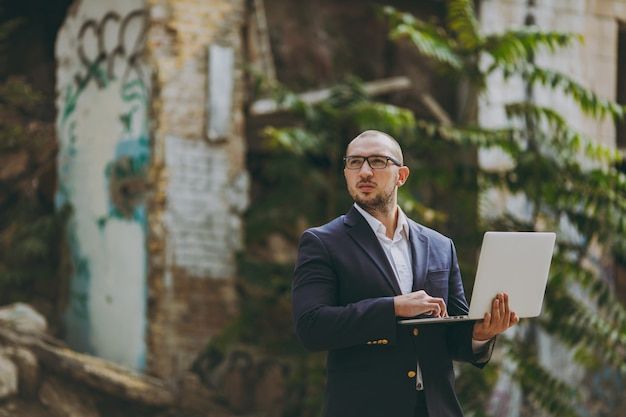 Jeune homme d'affaires intelligent réussi en chemise blanche, costume classique, lunettes. homme debout et travaillant sur un ordinateur portable près des ruines, des débris, des bâtiments en pierre à l'extérieur. bureau mobile, concept d'entreprise.
