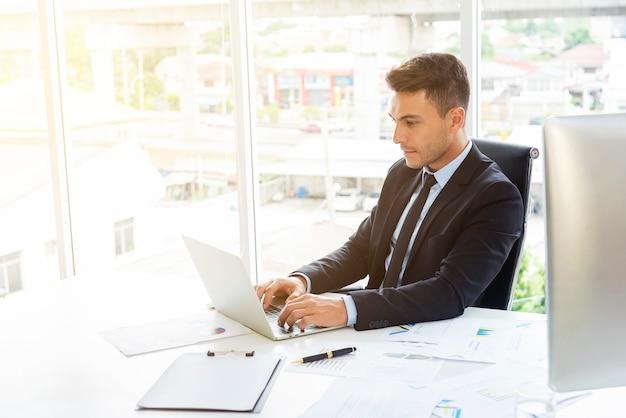 Jeune homme d'affaires intelligent travaillant avec un ordinateur portable sur le bureau dans un bureau moderne.